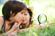 Happy kid exploring nature with magnifying glass